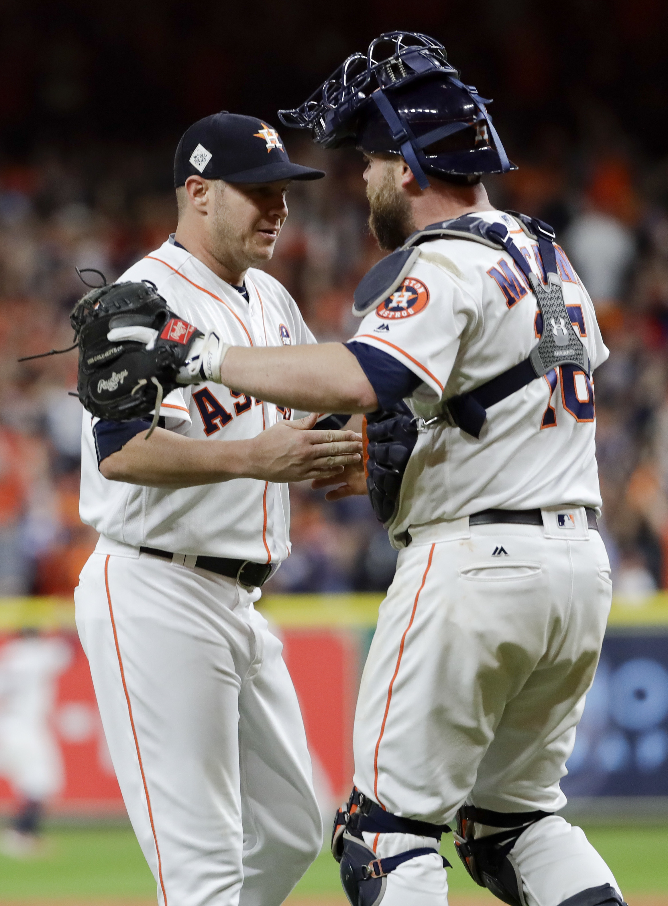 Houston Astros starting pitcher Brad Peacock, left, and catcher Brian McCann celebrate after their win against the Los Angeles Dodgers during Game 3 of baseball's World Series Friday, Oct. 27, 2017, in Houston. The Astros won 5-3 to take a 2-1 lead in the series. (AP Photo/Matt Slocum)