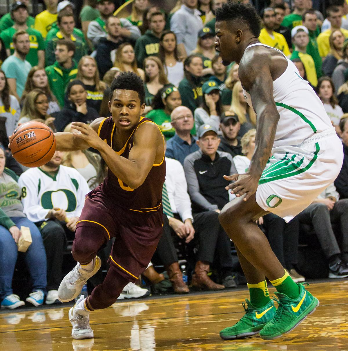 Arizona State guard Tra Holder (#0) dribbles past Oregon forward Jordan Bell (#1). Holder finished the evening with 17 points and 2 rebounds. The Oregon Ducks defeated the Arizona State Sun Devils 71 to 70. Photo by Ben Lonergan, Oregon News Lab