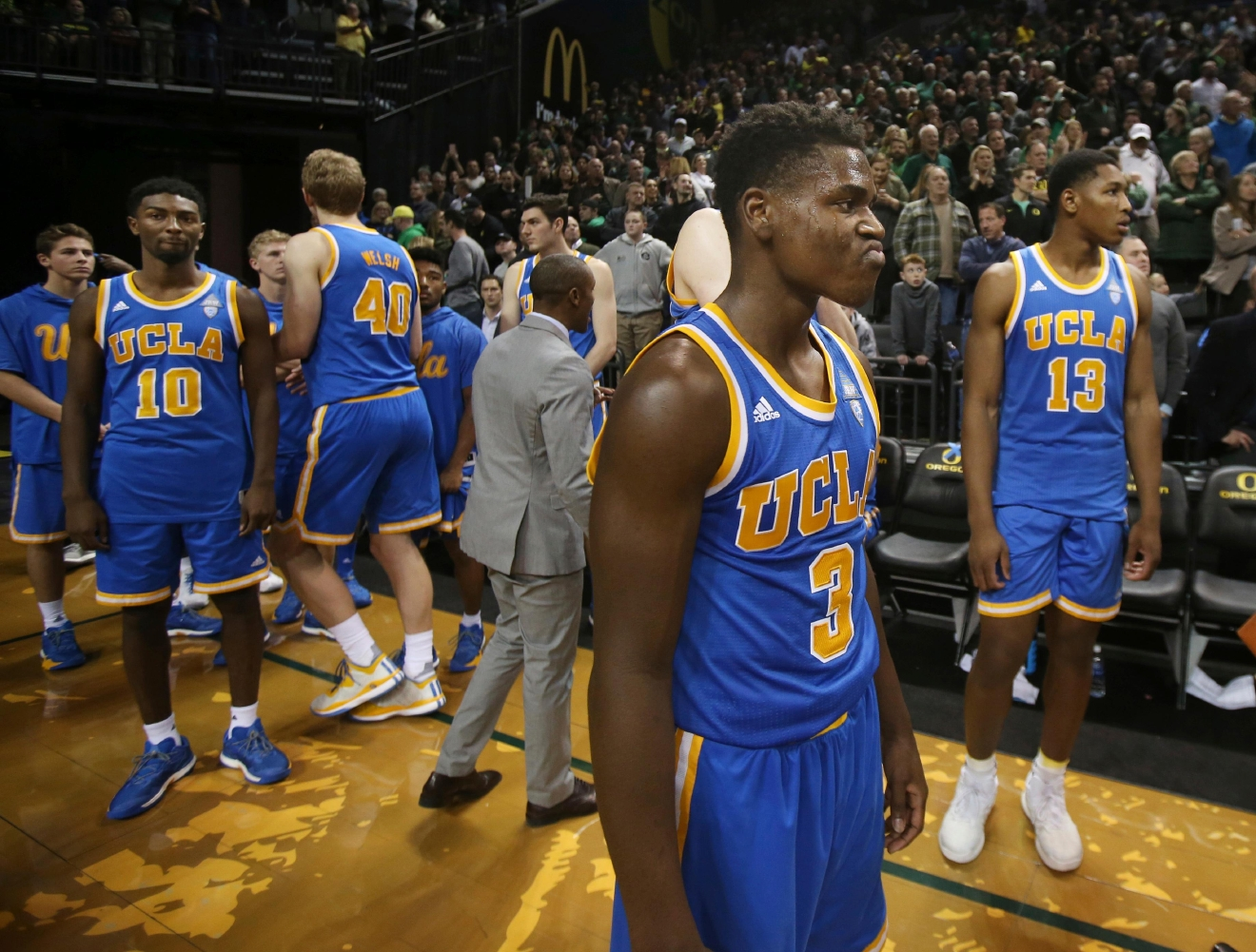 UCLA players including Aaron Holiday, center, and Ike Anigbogu, right, look on as officials try to clear the floor so the game can resume after Oregon's Dillon Brooks sunk a shot with .08 seconds left to play in an NCAA college basketball game Wednesday, Dec. 28, 2016, in Eugene, Ore. (AP Photo/Chris Pietsch)
