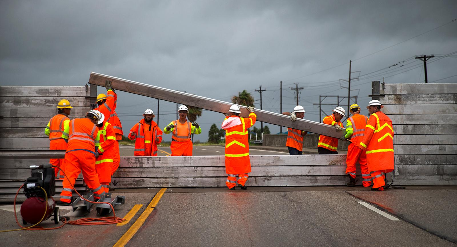 "TxDOT crews install the final portion of a surge wall on TX-361 leading to the Port Aransas ferry in Aransas Pass, Texas, on Friday, Aug. 25, 2017. Conditions deteriorated Friday along the Texas Gulf Coast as Hurricane Harvey strengthened and crawled toward the state, with forecasters warning that evacuations and preparations ""should be rushed to completion.""   (Nick Wagner /Austin American-Statesman via AP)"