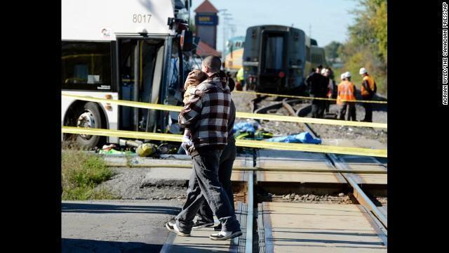 A man carries a child past the scene of the crash on September 18.