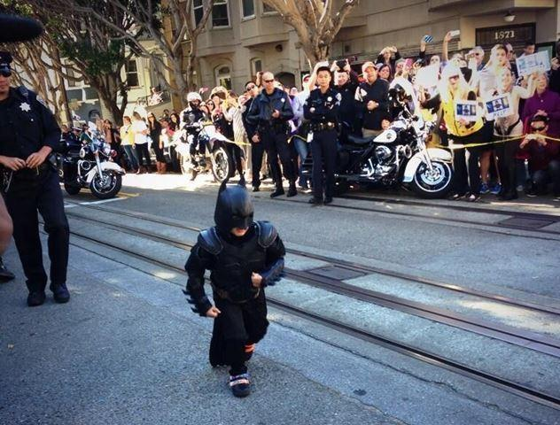 Batkid is cheered on by fans in the streets as he makes his way to scene.