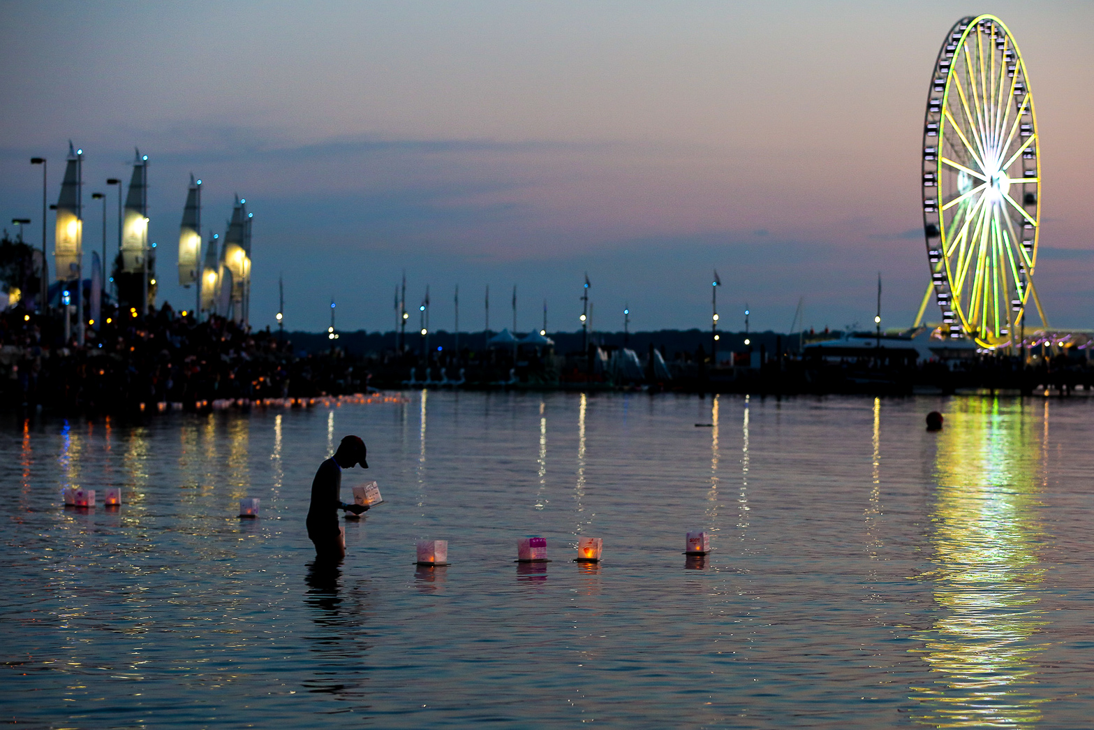 A boy puts a lantern in the water during the water lantern festival at National Harbor in August.{&nbsp;}(Amanda Andrade-Rhoades/DC Refined)<p></p>