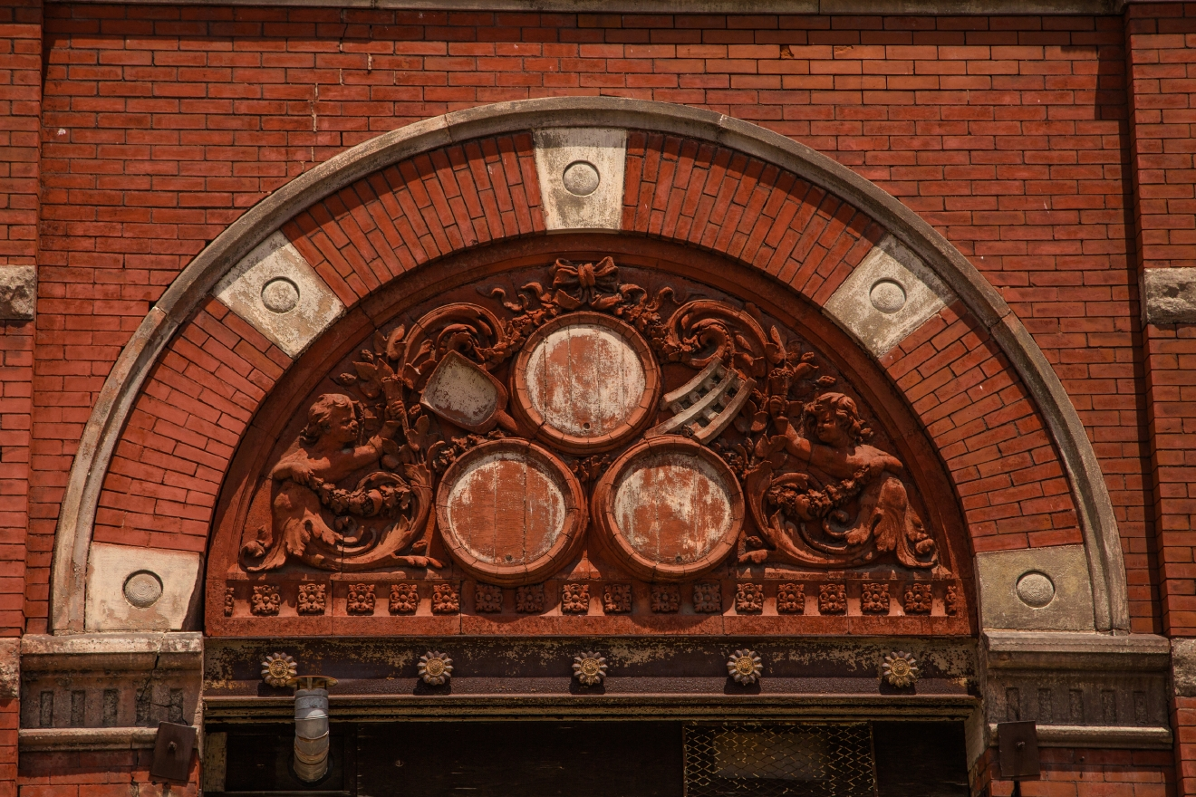 An ornate pediment with intricately carved imagery that references the brewing industry on the old Sohn/Clyffside Brewery on W. McMicken Avenue. / Image by Catherine Viox