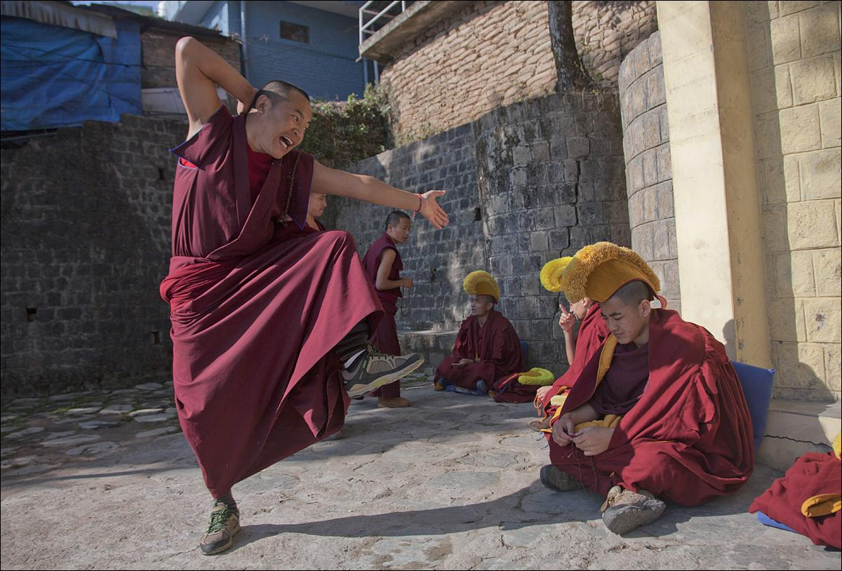 An exile Tibetan monk gestures as he makes a point in a dialectics debate with another monk, sitting right, at the Kirti monastery in Dharmsala, India, Monday, Jan. 18, 2016. The debate is an essential part of their training as Buddhist monks. (AP Photo/Ashwini Bhatia)