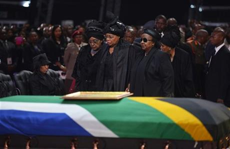Winnie Madikizela-Mandela, left, Nelson Mandela's former wife, left and Nelson Mandela%u2019s widow Graca Machel stand over the former South African president's casket during his funeral service .