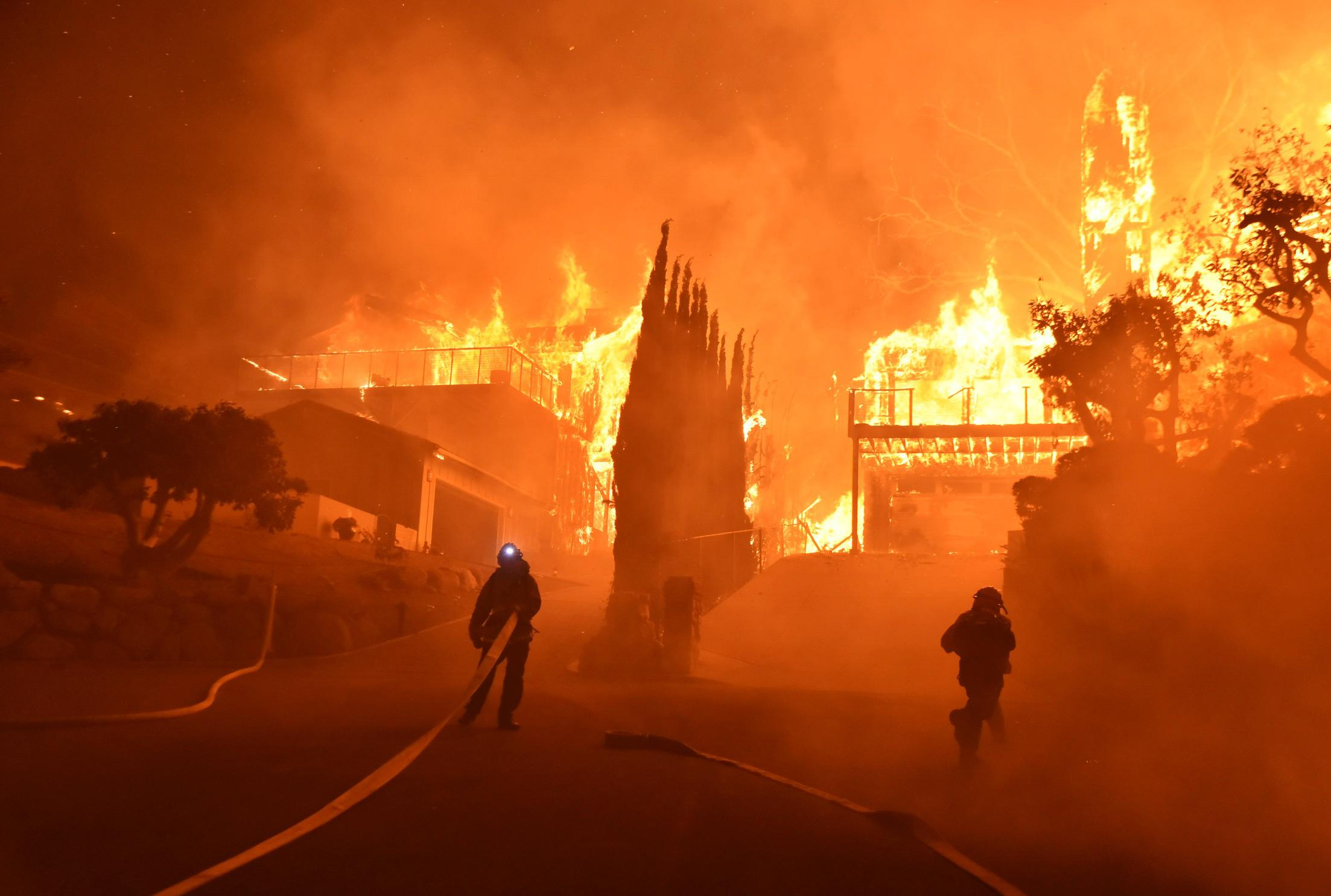 In this photo provided by the Ventura County Fire Department, firefighters work to put out a blaze burning homes early Tuesday, Dec. 5, 2017, in Ventura, Calif.  (Ryan Cullom/Ventura County Fire Department via AP)