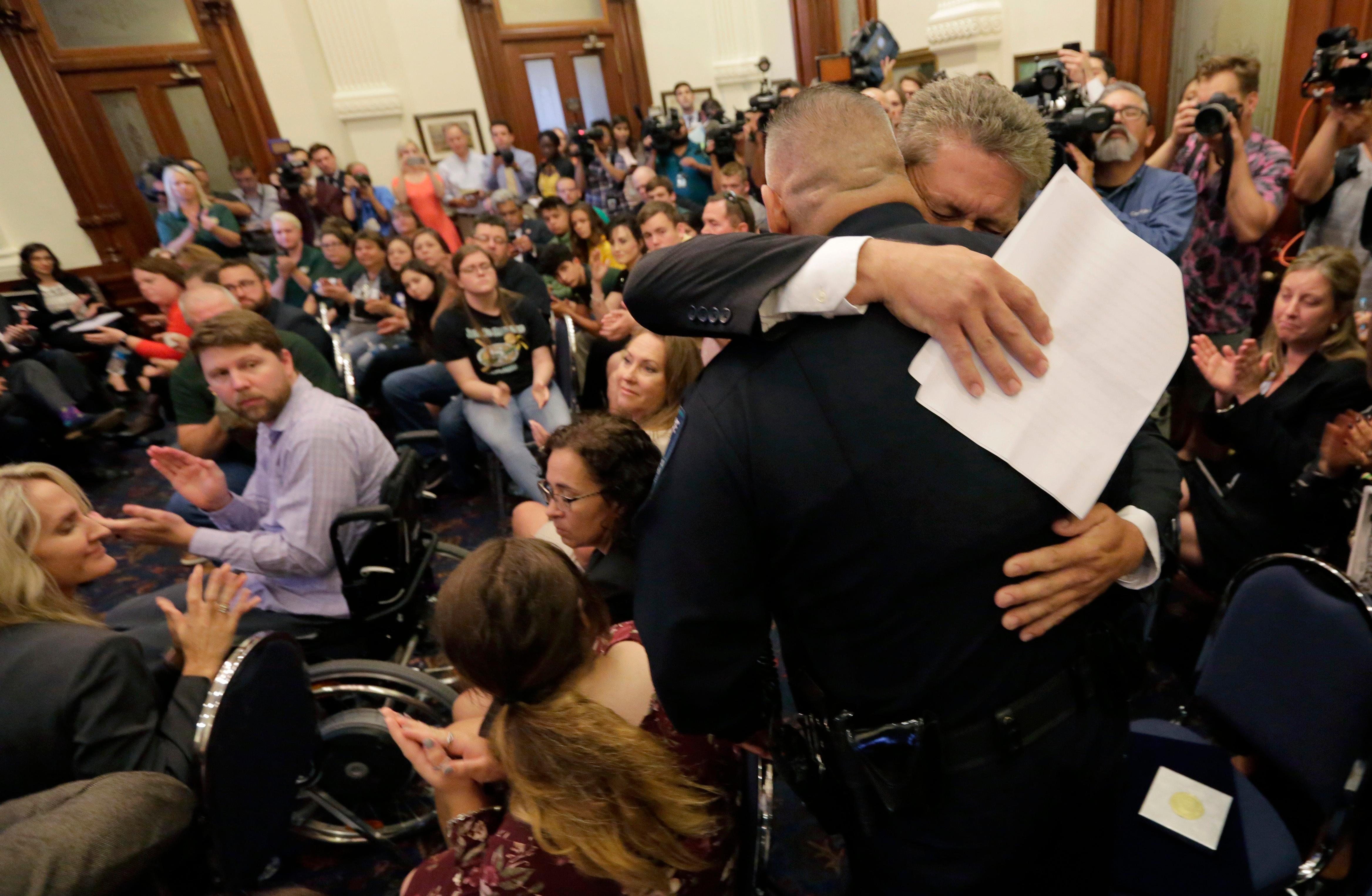 Scot Rice hugs Santa Fe Independent School District police officer John Banda after telling his story during a roundtable discussion in Austin, Texas, Thursday, May 24, 2018, hosted by Texas Gov. Gregg Abbott to address safety and security at Texas schools in the wake of the shooting at Sante Fe, Texas. Rice's wife Flo Rice, a substitute teacher, was carried from the Santa Fe scene of last week's school shooting by officer Banda after she was shot in the leg. (AP Photo/Eric Gay)