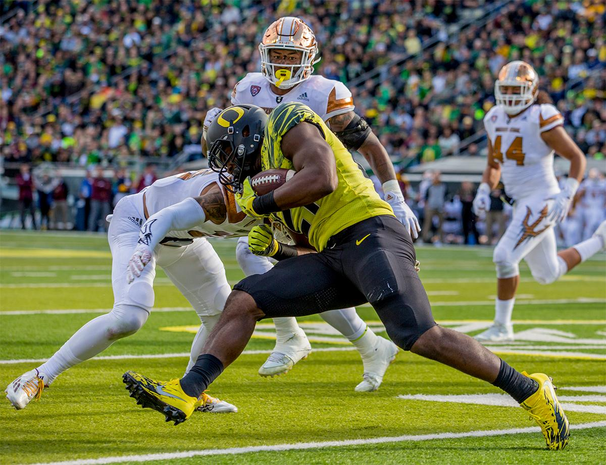 The Duck's Royce Freeman (#21) runs the ball down the field as Sun Devils players converge on him. Oregon lead at the end of the 1st half 30-14. Photos by August Frank, Oregon News Lab