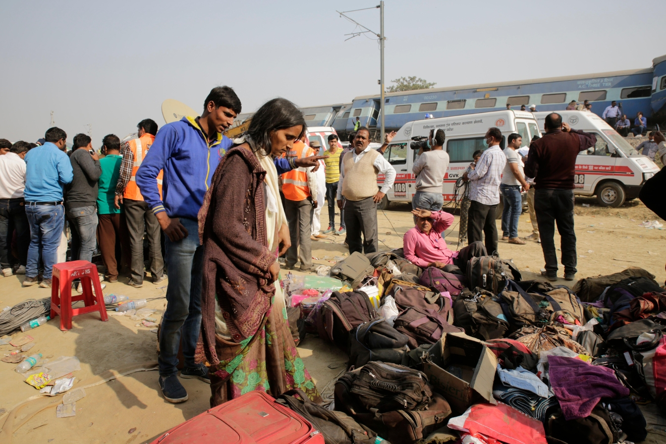 People stand near the belongings of passengers after 14 coaches of an overnight passenger train rolled off the track near Pukhrayan village Kanpur Dehat district, Uttar Pradesh state, India, Sunday, Nov. 20, 2016. Dozens were killed and dozens more were injured in the accident. (AP Photo/Rajesh Kumar Singh)