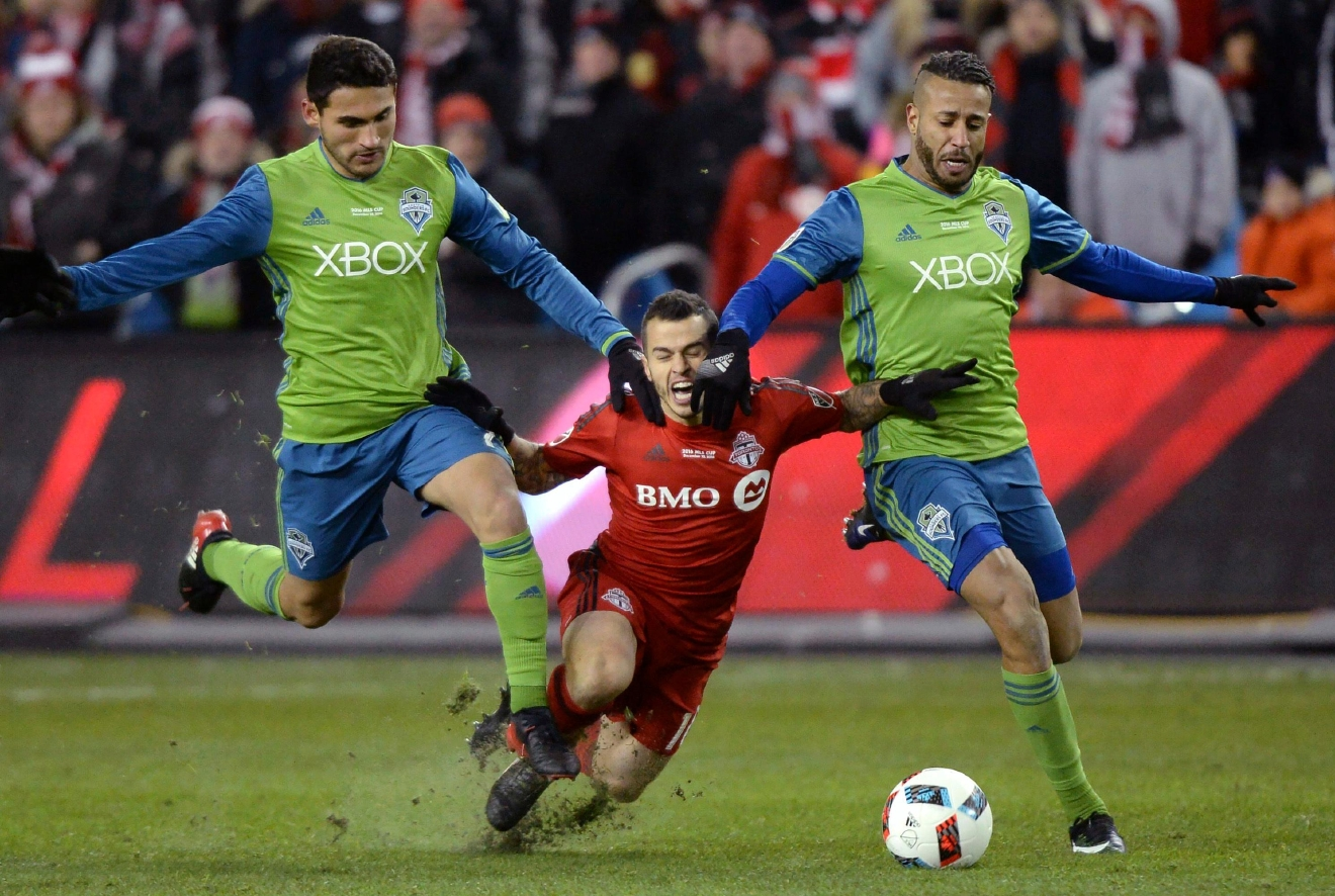 Toronto FC forward Sebastian Giovinco, center, is sandwiched between Seattle Sounders midfielder Cristian Roldan, left, and Tyrone Mears, right, during second-half MLS Cup final soccer action in Toronto, Saturday, Dec. 10, 2016. (Nathan Denette/The Canadian Press via AP)