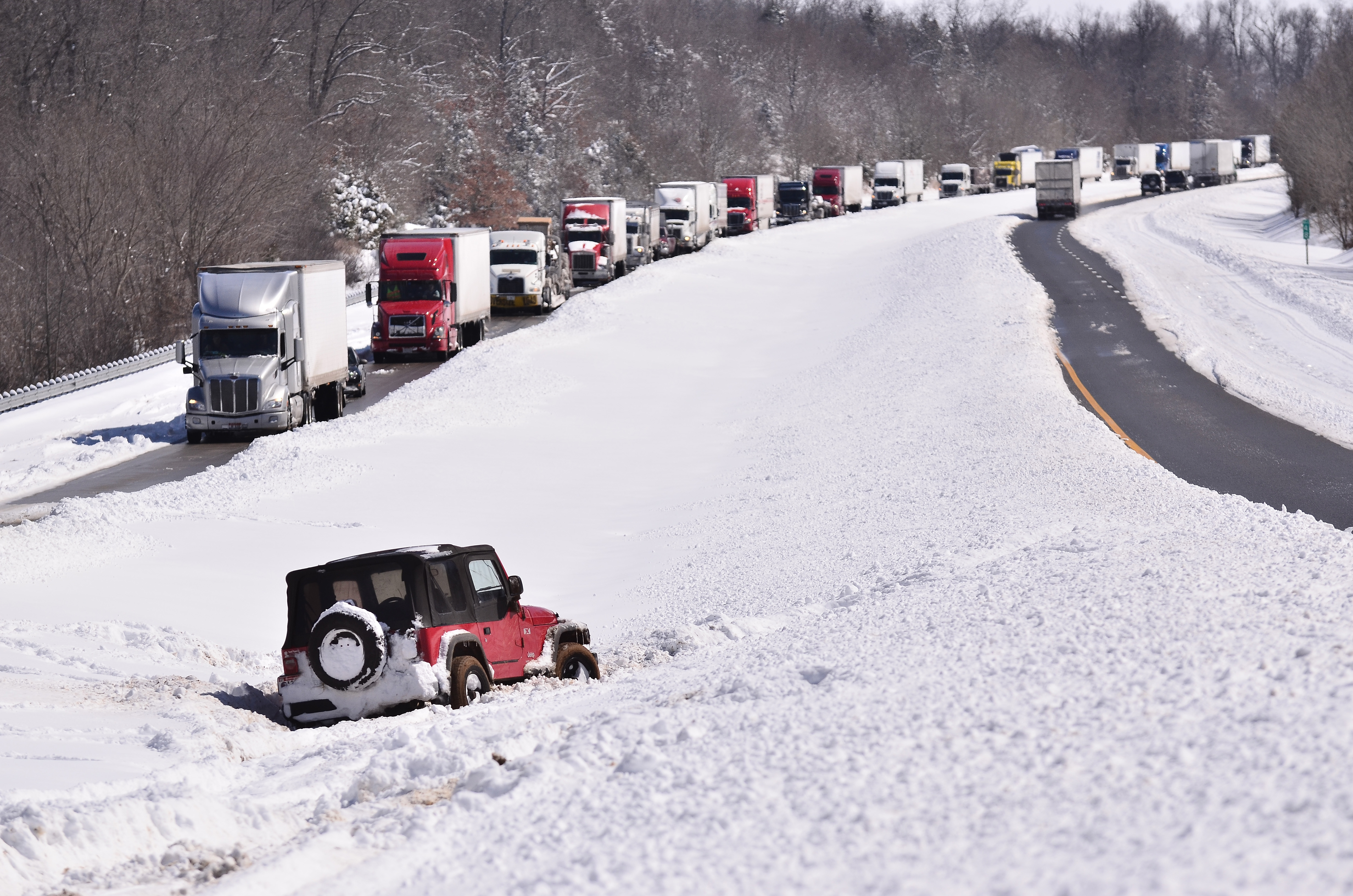 A vehicle sits in the median of Interstate 24 as drivers wait after being stranded between Eddyville and Cadiz, Ky., Thursday, March 5, 2015. Interstate 24 between Paducah and Cadiz was closed after nearly a foot of snow fell in the region. (AP Photo/Stephen Lance Dennee)